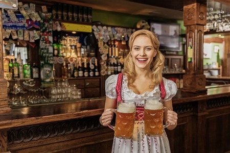 Outgoing woman carrying cups of beer