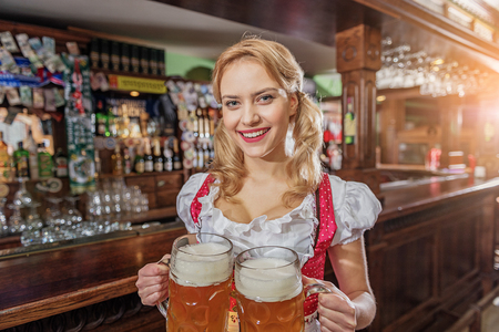 Cheerful female serving alcohol in pub