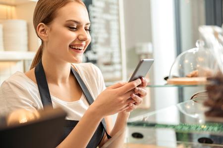 カフェでスマート フォンでのメッセージング幸せ女性労働者 写真素材
