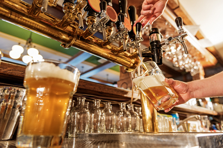 Male arm pouring beer in tap-room