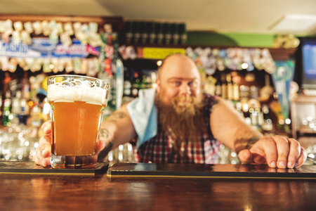 alehouse: Man arm putting alcohol beverage in alehouse Stock Photo