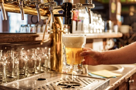 Male arm keeping pouring beer in alehouse Stock Photo