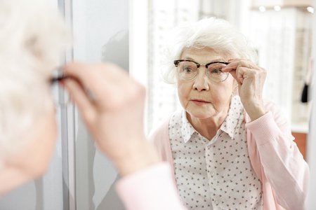 Interested mature lady glancing on mirror Stock Photo