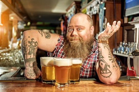 Surprised fat male drinking beverage