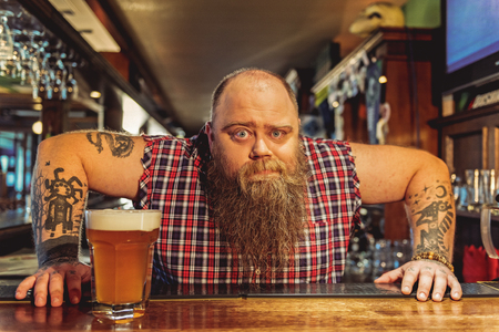 Surprised bearded male working in pub