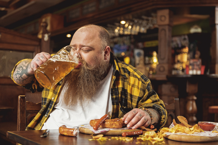 Glad obese male tasting alcohol in pub Stock Photo