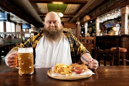 Glad fat male sitting in pub Stock Photo