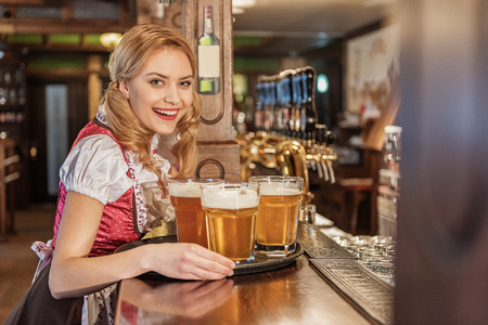 Happy young waitress carrying beverage