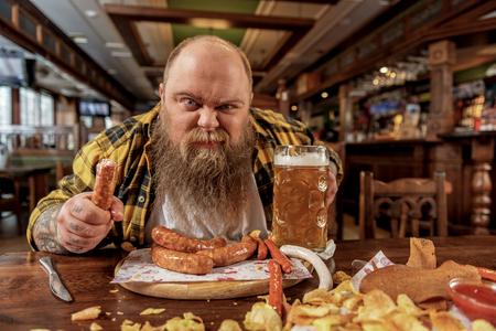 粗脂肪の男性のパブでフランクフルトを試飲