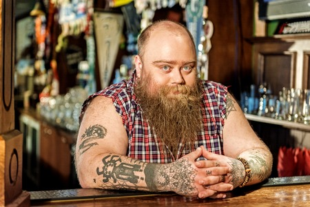 Calm bearded male expecting visitors in beerhouse Stock Photo
