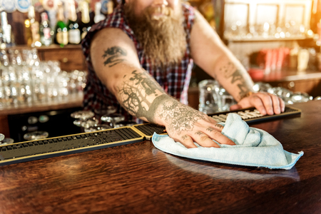 Man arm wiping counter in beerhouse