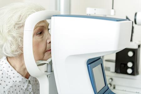 光学機器のそばに座って深刻な老婆
