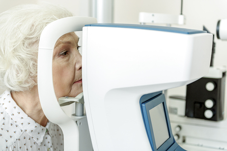 Serious old woman sitting near optical apparatus