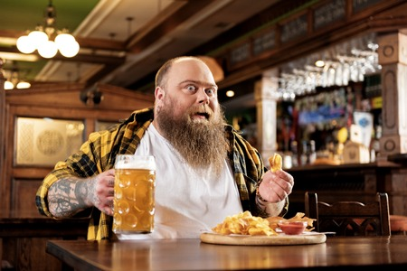 Cheerful bearded man eating chips in bar