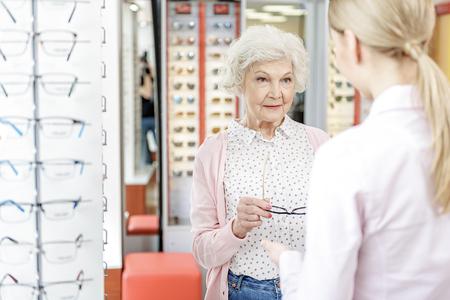 Curious mature woman keeping eyewear