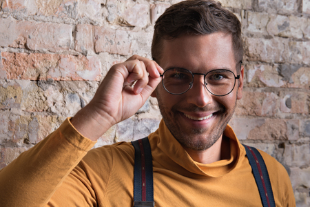 Positive young bearded man posing with smile