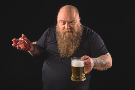 fatso: Male fatso drinking lager with raw meat