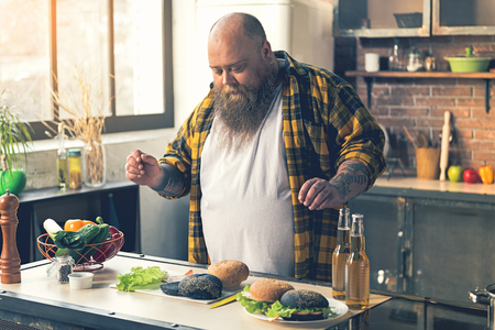 fatso: Male fatso preparing tasty burgers