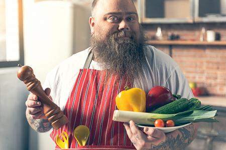 fatso: Joyful male fatso presenting healthy food