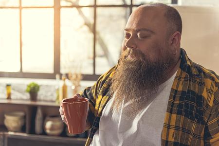 fatso: Happy male fatso enjoying hot drink in kitchen