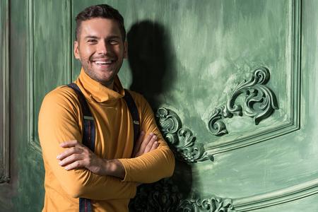 Gleeful jeune mec avec chaume contre mur vert Banque d'images - 77761560