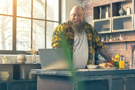 fatso: Cheerful male fatso entertaining with laptop in kitchen Stock Photo