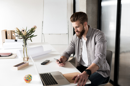 Busy office worker using phone Фото со стока