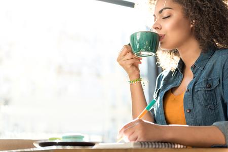Pleasure woman drinking coffee in cafe