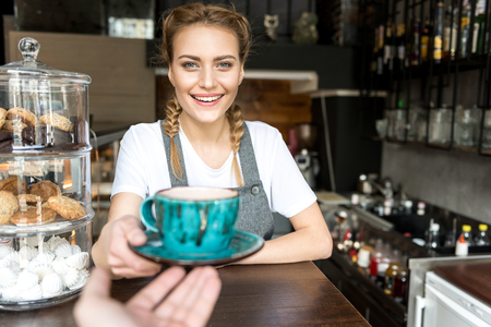 Cheerful female holding out mug to visitor