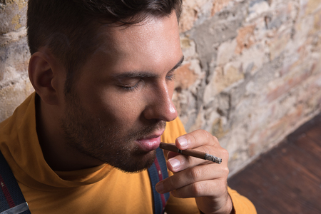 Youthful rueful male holding cigarette