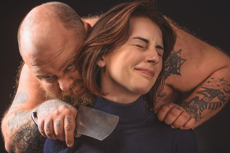 Hungry thick guy threatening to young woman with knife Stock Photo