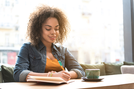 Outgoing woman making notes in scribbling-diary
