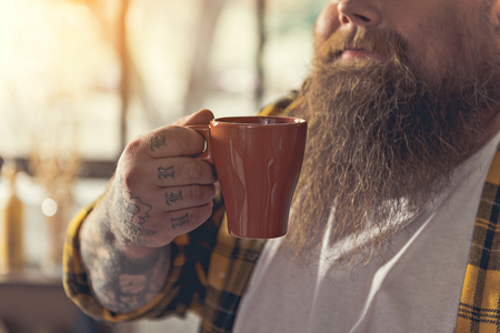 Cheerful thick guy drinking hot beverage Stock Photo
