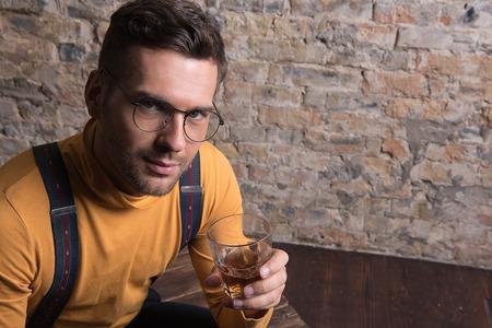 Youthful guy sitting and drinking alcohol Stock Photo