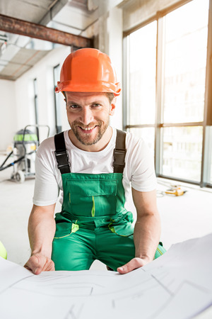 Happy smiling constructor keeping plan
