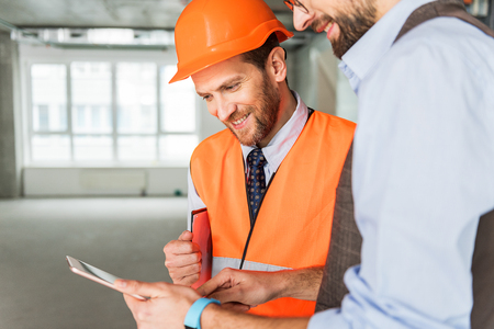 Hilarious smiling builders keeping gadget Stock Photo