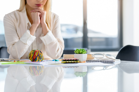 Wonderland. Reflection of different colored things in worktable. Elegant woman sitting at desk in background. Copy space in the right side Stock Photo