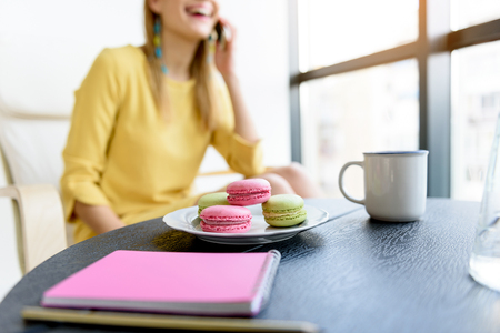 Stylish young woman eating colored macaroons