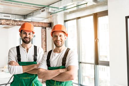 Hilarische glimlachende constructeurs die handen vouwen Stockfoto