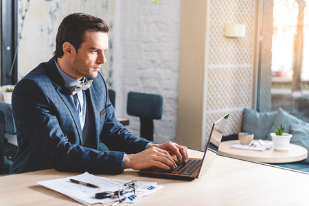 Orderly male working at laptop Stock Photo