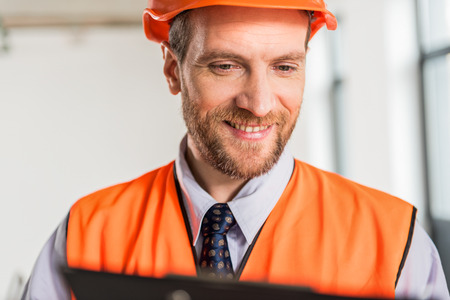 Jolly smiling constructor wearing hardhat Stock Photo