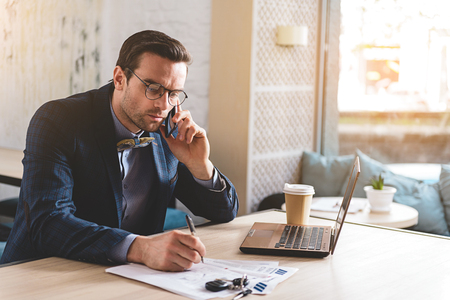 private room: Serious male telling at cellphone in office Stock Photo