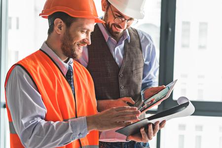 Joyful smiling builders checking documents
