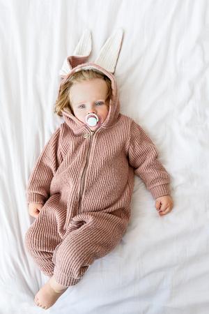 Innocent toddler in jumper on bedding Stock Photo
