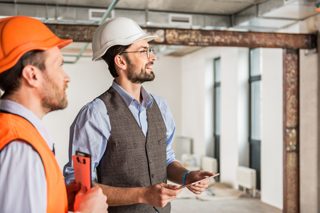 Interested smiling constructors glancing ahead Stock Photo