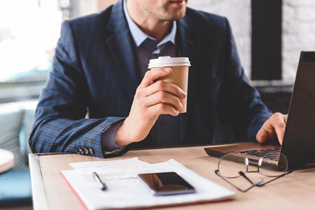 Serious businessman tasting beverage in office