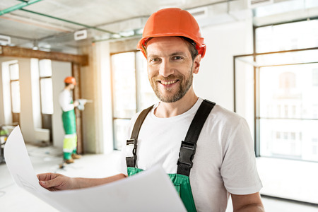 Jolly smiling builder keeping drafts Stock Photo