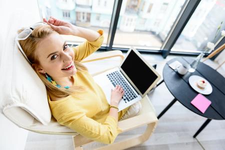 yellow notepad: Joyful girl laboring in white chair Stock Photo