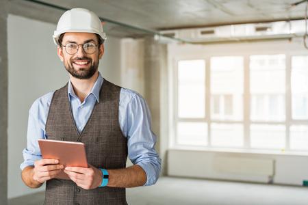 Happy smiling foreman keeping gadget
