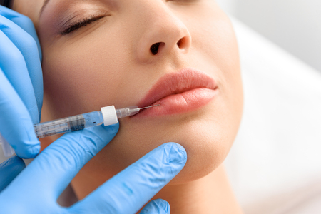 Serene woman enduring ache from syringe in clinic Stock Photo